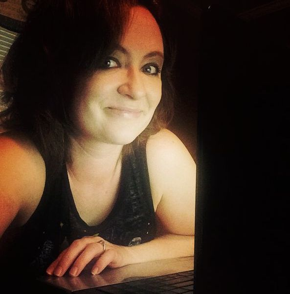[Me sitting in front of my laptop a few months ago and looking super writer-ly. I was probably actually on Facebook.]